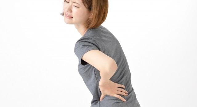 腰に痛みを感じている女性のイラスト